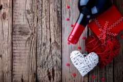 Gift ,  heart and the bottle of red wine for a romantic holiday Valentine's day on vintage wooden background.Celebration of Love and Happiness..Vintage style.selective focus.